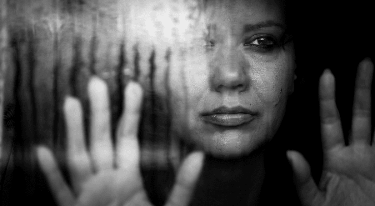 Domestic Violence Isolation: Woman stares out window trapped inside.