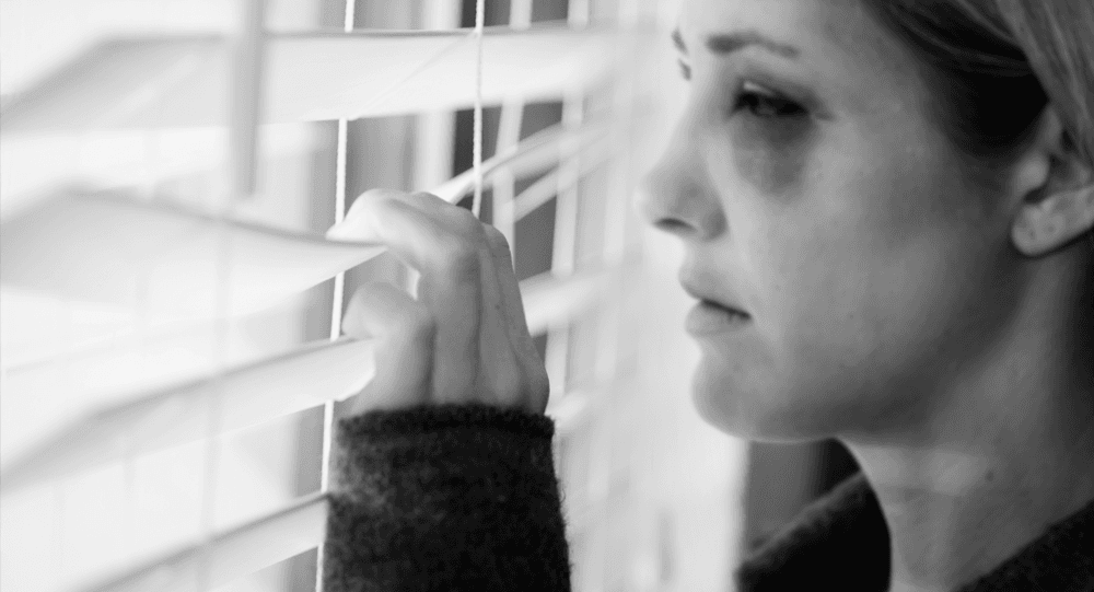 Woman with black eye looks out at the world from behind a window shade