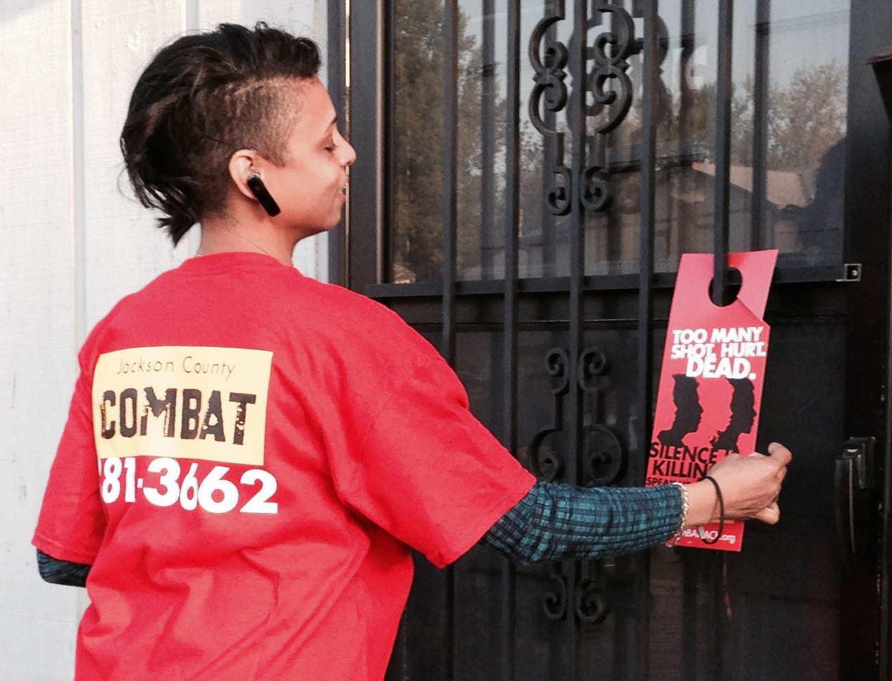 COMBAT volunteers places door hanger that highlights crime hotline phone number